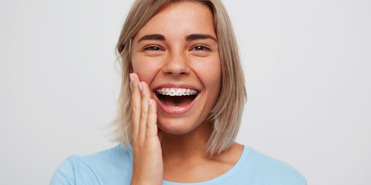 https://www.sorridibene.it/wp-content/uploads/2021/07/cheerful-beautiful-young-woman-with-blonde-hair-braces-teeth-laughing-touching-her-face-1280x640.jpg